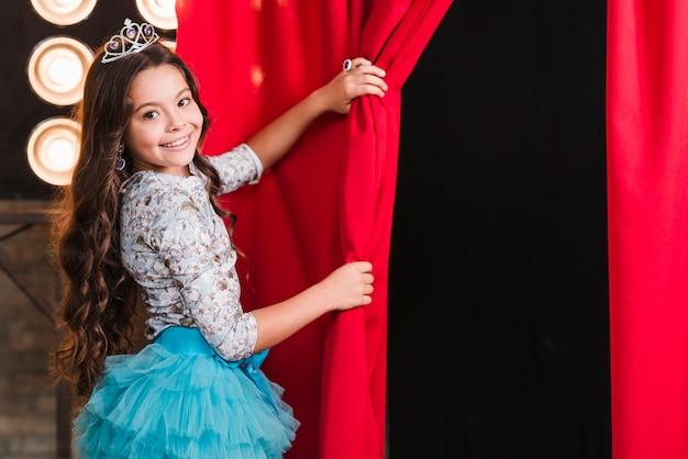 赤いカーテンを開く王冠を身に着けている笑顔の女の子