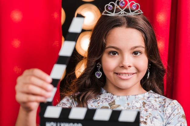 クラッパーボードを保持している王冠を身に着けている女の子の肖像