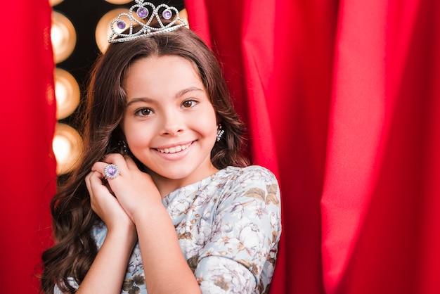 赤いカーテンの前に立つ王冠を着てかわいい女の子を笑って
