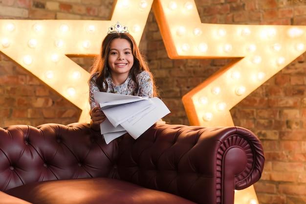 レンガの壁にソファの後ろに立つ笑顔の女の子