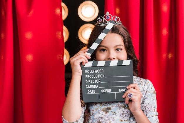 彼女の顔の前にクラッパーボードを保持している王冠を身に着けている女の子の肖像