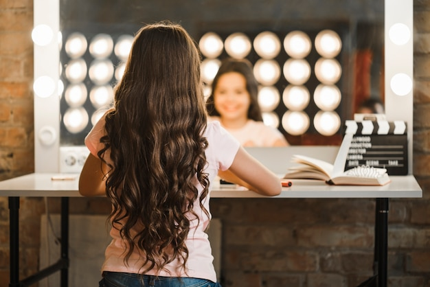 メイクアップルームに座って長いブルネットの波打った髪の女の子の背面図
