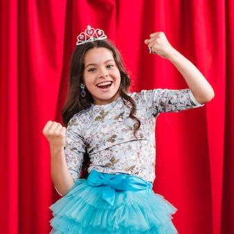 赤いカーテンの前に立っている勝者のジェスチャーを作る陽気でかわいい女の子