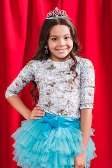 赤いカーテンの前に立っている笑顔の女の子の肖像