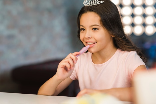 彼女の唇に口紅を適用する笑顔の若い女の子の反射