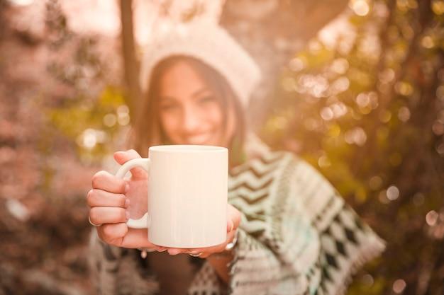 森の中でマグカップを示しているぼんやりした女性