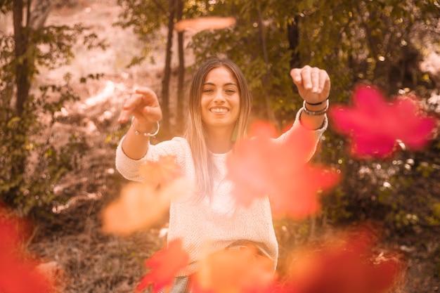 カメラに秋の葉を投げる女性