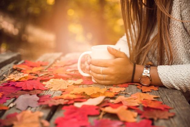 秋の公園のテーブルでマグカップを持つ女性を作物