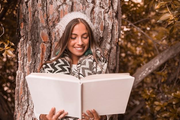 Прекрасная женщина, читающая книгу возле дерева
