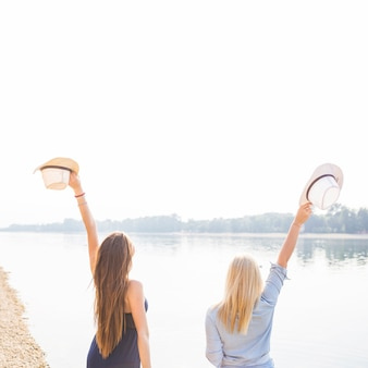 湖の近くで帽子を持って手を上げる女性のリアビュー