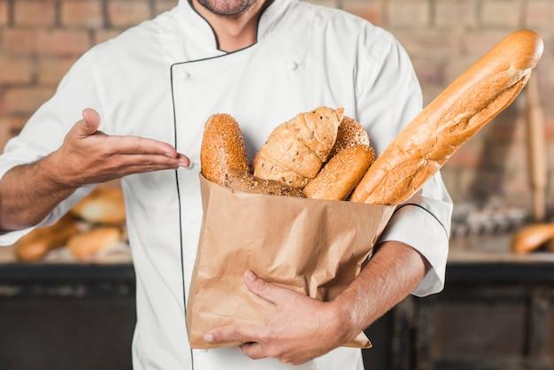 Мужской пекарь показывает буханку хлеба в коричневом бумажном мешке