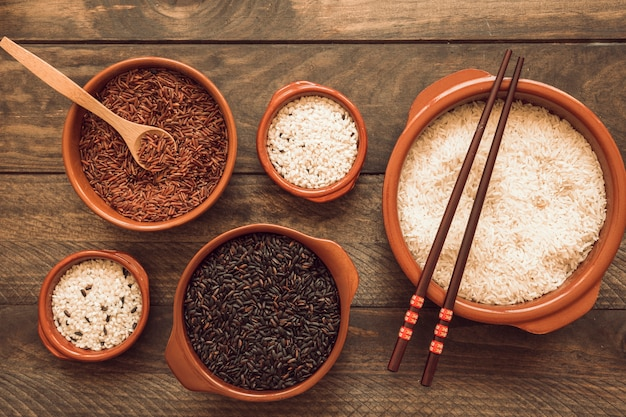 赤のボウル;茶色の白米と木製のスプーンと箸