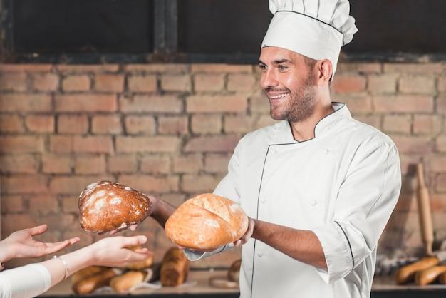 Улыбаясь мужской пекарь, давая два хлеб булочки для женщин-клиентов