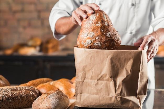 Муж пекарь положить испеченный хлеб в коричневый бумажный мешок