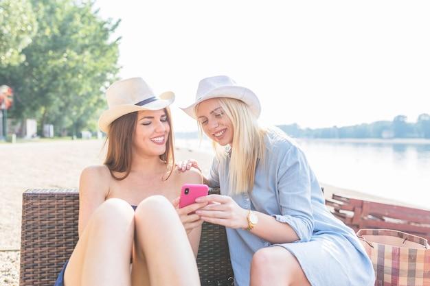 Привлекательные молодые женщины, сидя на пляже, глядя на мобильный телефон