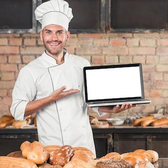 異なるタイプのパンを持つテーブルの前に立っている男性のベーカリーを笑顔で