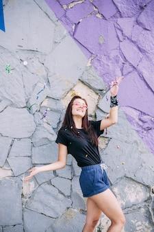 Молодая девушка, ставит перед окрашенной каменной стеной
