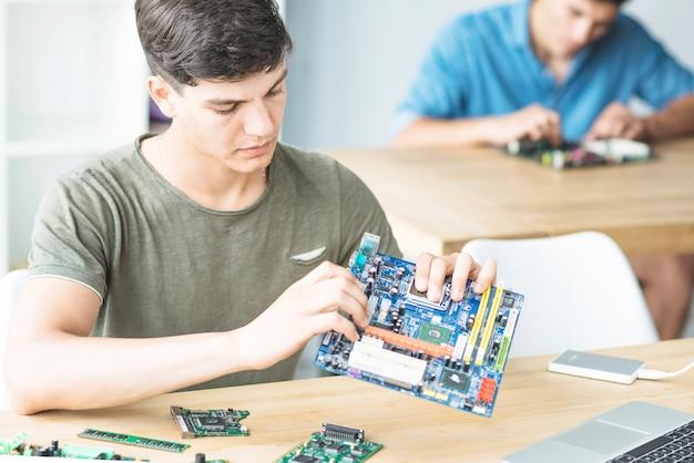 若い学生がマザーボードを組み立てることを学ぶ