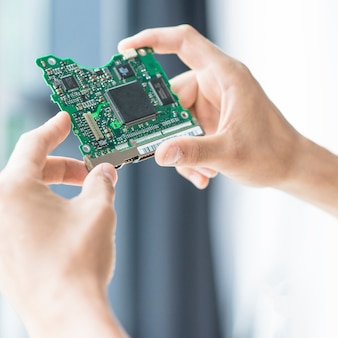 ハードディスク、回路基板を持っている手のクローズアップ