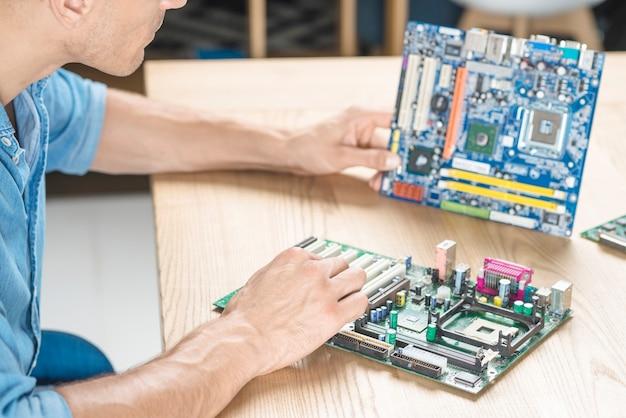 木製テーブル上のマザーボードをアップグレードする技術者