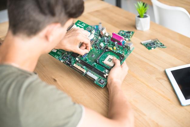 コンピュータのハードウェア機器を修復する男のオーバーヘッドビュー