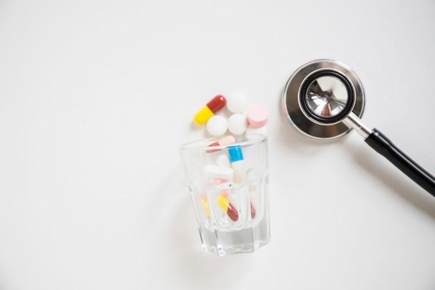 Красочные таблетки и капсулы, пролитые стетоскоп на белом фоне