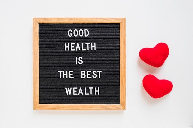 赤いぬいぐるみの黒いボード上の健康メッセージ