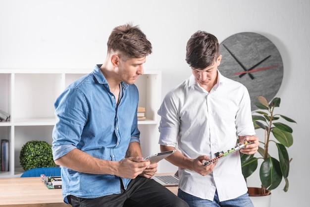 Два мужчины-техника, занимающиеся цифровой планшетной и компьютерной материнской платой