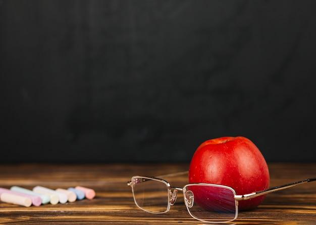 眼鏡の近くに赤リンゴ