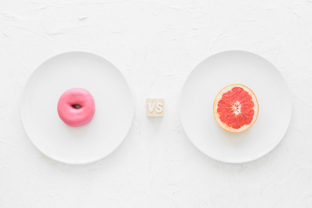 Розовый пончик против половины грейпфрутов на белой тарелке на фоне