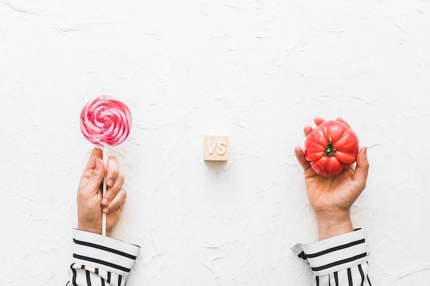 ロリポップと赤いトマトを手にした手のオーバーヘッドビュー