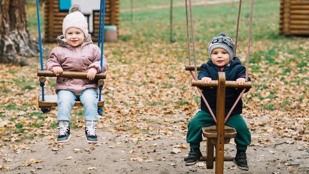 木製のシーソーでスイングする幼児の子供たち