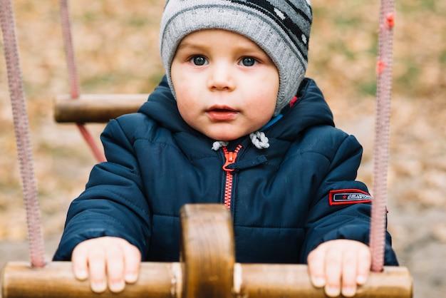Мальчик с голубыми глазами в теплой одежде на качелях