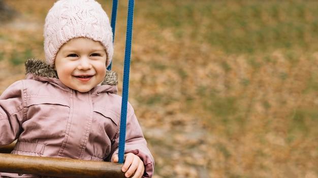 秋の公園のスイングで暖かい服を着た幼児の女の子
