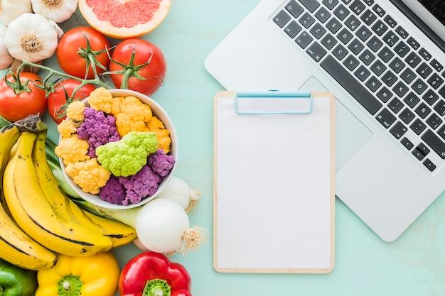 空のクリップボードと机の上のラップトップと健康食品
