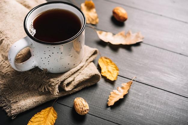 Крупные ядра и листья рядом с напитком и тканью