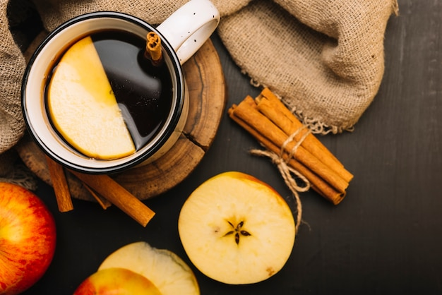 Яблоко и корицы возле ткани и пряного напитка