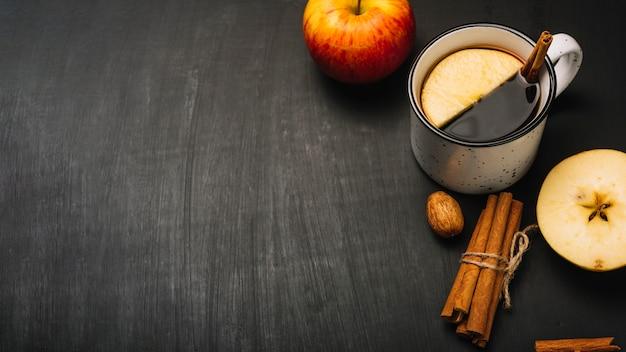 Корица и яблоки возле пряного напитка