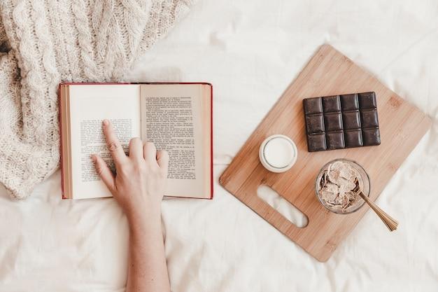 Рука следующий текст в книге возле еды на кровати