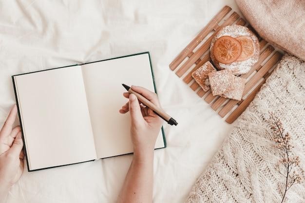 手、ペン、開いた、ノート、ベッド