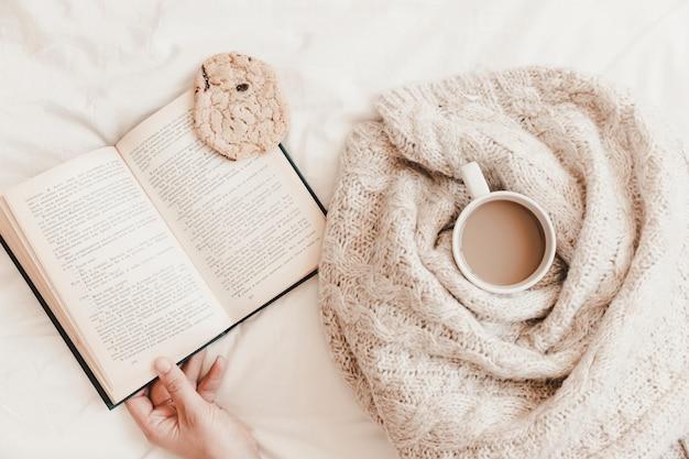 Рука, держащая книгу с печеньем на ней возле теплого напитка в плед