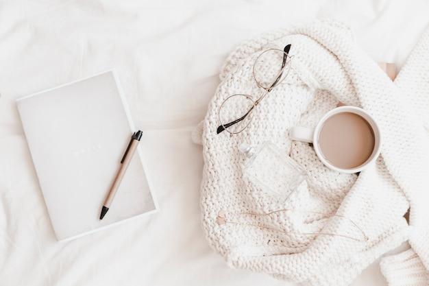 セーターの近くにベッドシート上のものでペンが付いているノートブック