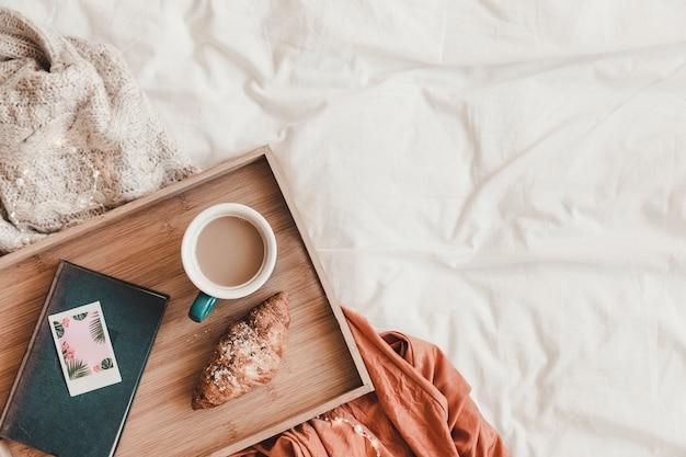 ベッド上の本の近くにクロワッサンとコーヒー
