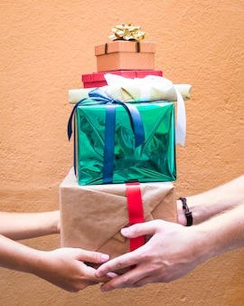 オレンジの背景に贈り物のスタックを保持するカップルの手