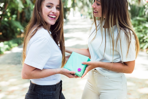 女性、公園で彼女の幸せな友人にプレゼントを与える