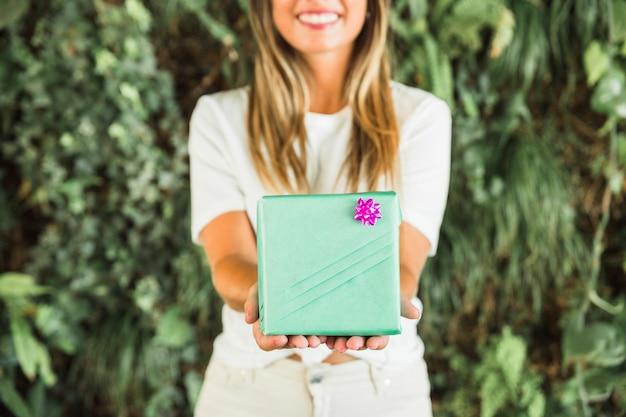 緑色のギフトボックスを保持している女性の手のクローズアップ