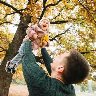 秋の森で娘と遊ぶお父さん
