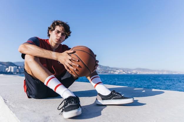 海の近くに座っているバスケットボールの十代の少年