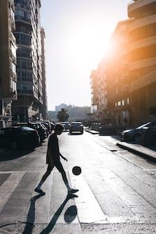 街の通りでバスケットボールをしている十代の少年のシルエット