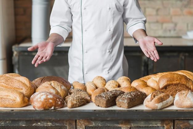様々な焼きたてのパンを示すパン屋さんの手